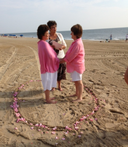 Two women getting married at the beach, standing in a circle of flowers with Rev Sharon